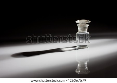 Empty vintage glass bottle isolated on a dark background with shadows - stock photo