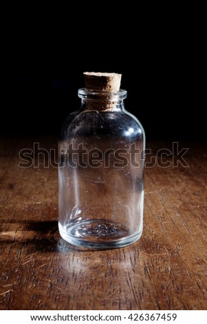 Empty vintage glass bottle isolated on a wooden background with shadows - stock photo