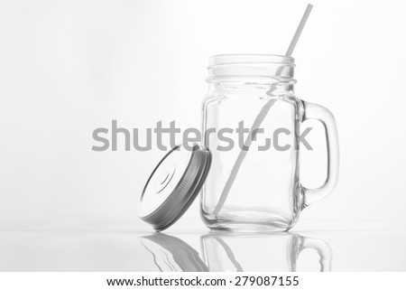 Empty vintage mason Jar  having lid and handle with straw on White background with reflection and copy space - stock photo