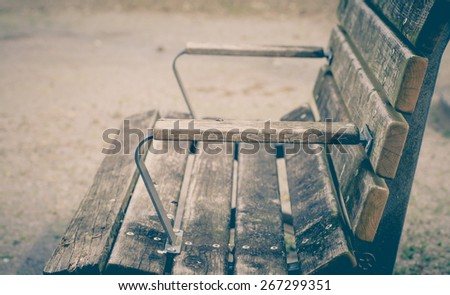 Empty vintage old wooden bench at public playground - stock photo