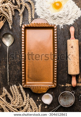 Empty vintage rustic tart mold with kitchen utensil for bake and ears on rustic wooden background, top view - stock photo