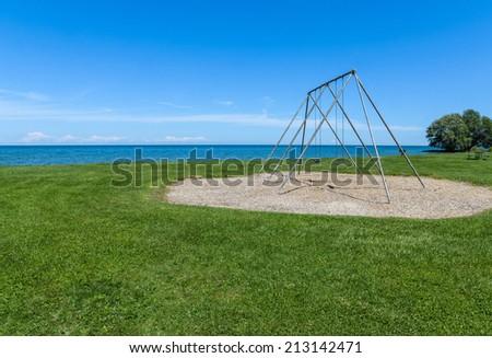 Empty Vintage Swings Beside Lake - stock photo