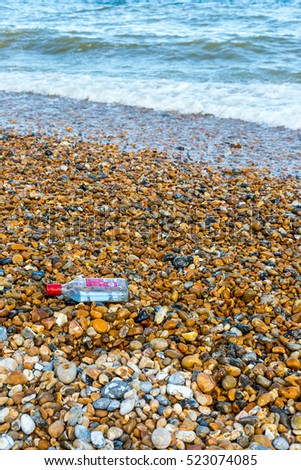Empty vodka bottle with red cap on stone beach with sea waves in background
