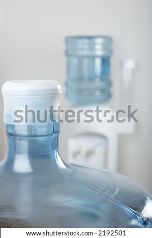 Empty water bottle front of office water cooler - stock photo