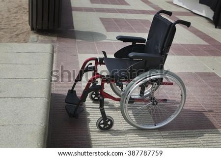 Empty wheelchair on a beach near beach - stock photo