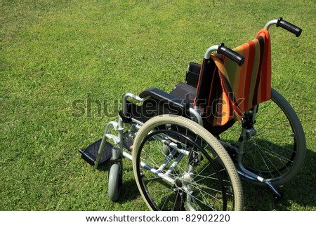 empty wheelchair over green grass - stock photo