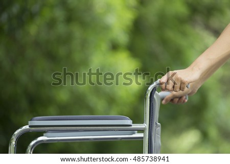 Empty wheelchair pushed by nurse's hands