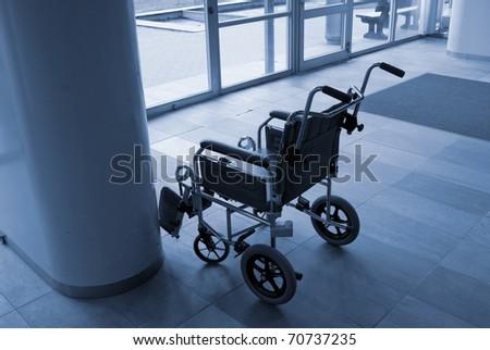 Empty wheelchair ready for use near a hospital entrance - Denmark. - stock photo