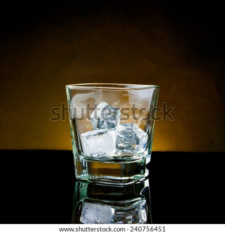 empty whiskey glass with ice and warm light on black table, with reflection - stock photo