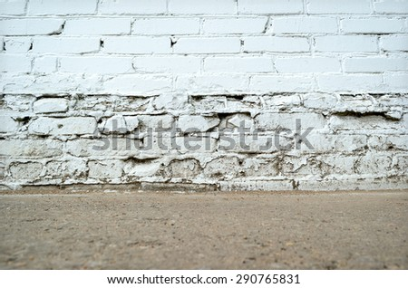 Empty white aged brick dirty wall with ground floor - stock photo