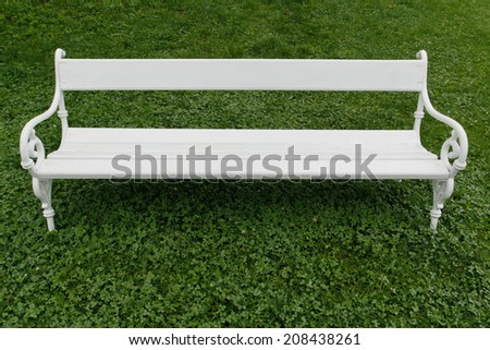 Empty white bench on wet grass