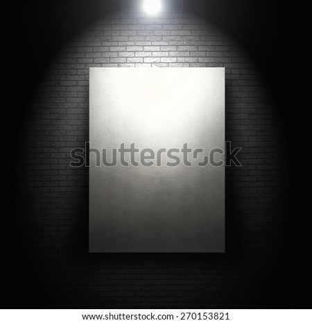 Empty white board in front of brick wall with spotlight - stock photo