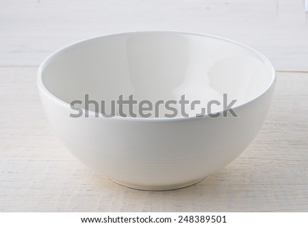 Empty white bowl on wooden table - stock photo