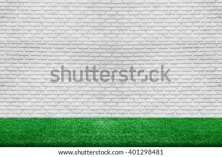 empty white brick wall and fresh green grass floor. the background for product display template. - stock photo