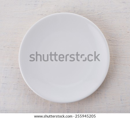 Empty white ceramic plate on wooden table - stock photo