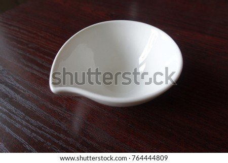 Empty white ceramic sauce boat with spout
