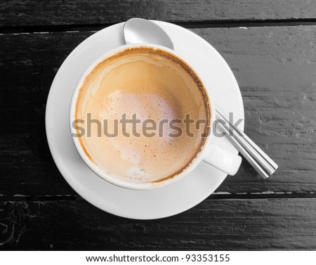 Empty white cup of hot coffee latte on dark wooden table - stock photo