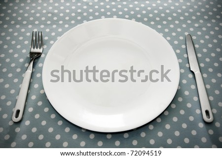 Empty white dinner plate with utensils on fun grey polka dot tablecloth. - stock photo