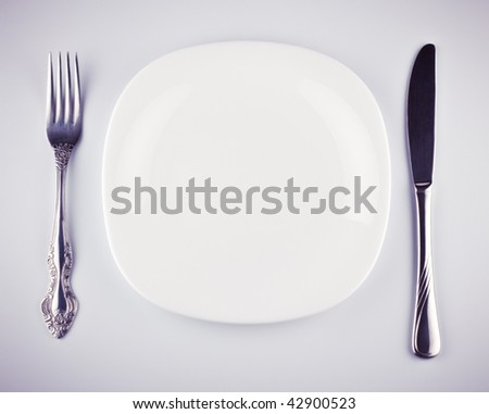 empty white dish knife and fork on grey background