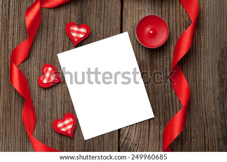 Empty white isolated frame with hearts, red candle and ribbons for valentine's day on wooden background - stock photo