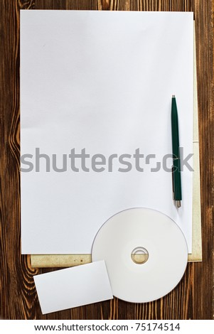 Empty white page with CD and business card on wooden background - stock photo