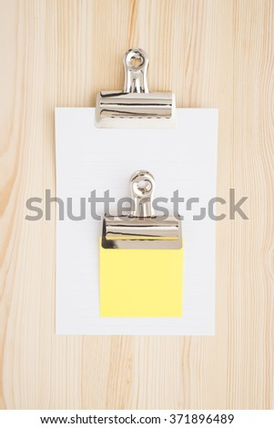 Empty white paper and sticky note on wooden table in office. - stock photo