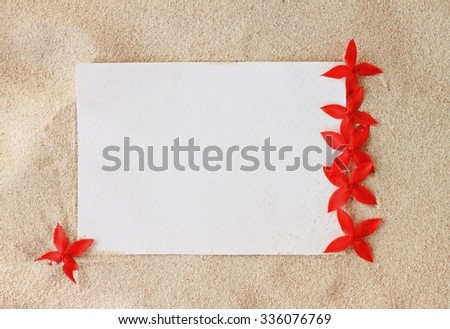 Empty white paper card notice space for writing text message on beige sea sand beach, adorned with bright red tropical flowers Ixora. - stock photo