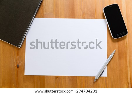 Empty White paper on desk with cellphone for adding information - stock photo