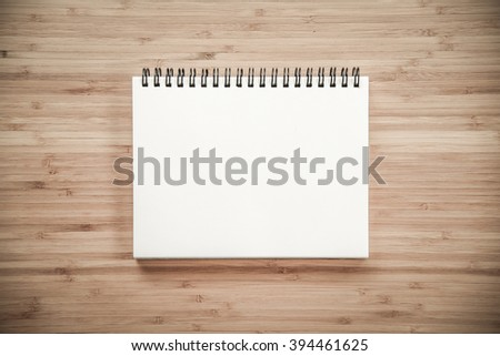 empty white paper page of binder notebook on wooden texture table top - use for background or backdrop in business presentation or education learning concepts