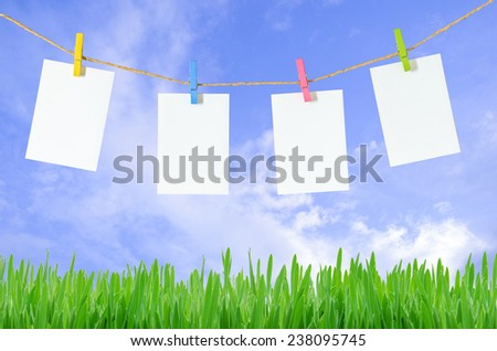 empty white photo frames hanging with clothespins on blue sky background  - stock photo