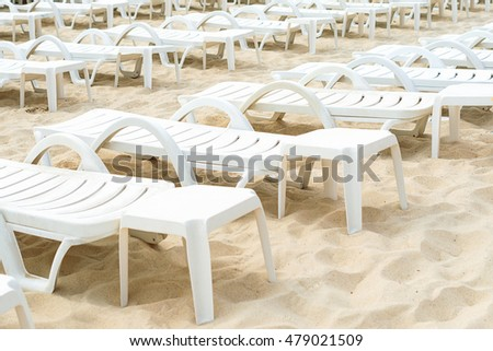 empty white plastic deck chairs on sandy beach - Beach Lounge Chairs