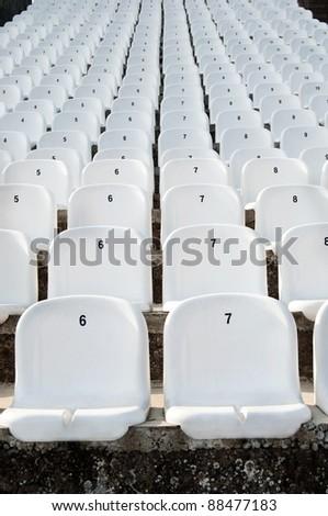 Empty white plastic seats in a stadium - stock photo
