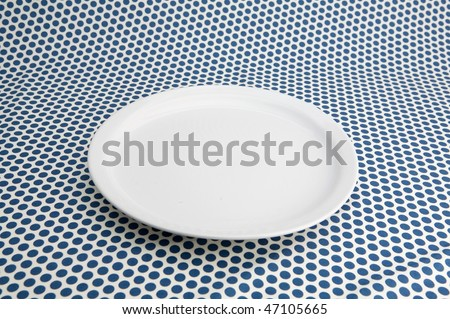 Empty white plat on table caver by blue tablecloth - stock photo