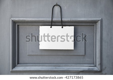 Empty white plate for information text hanging on gray wooden door - stock photo
