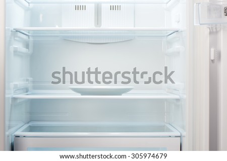Empty white plate in open empty refrigerator. Weight loss diet concept. - stock photo