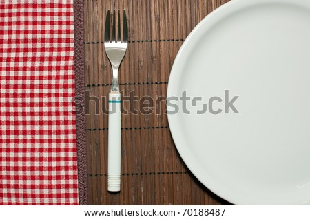 Empty white plate on a kitchen table, top view - stock photo