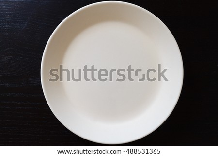 Empty white plate on black wooden table. Kitchen tools close up