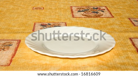 Empty white plate on bright yellow tablecloth - stock photo