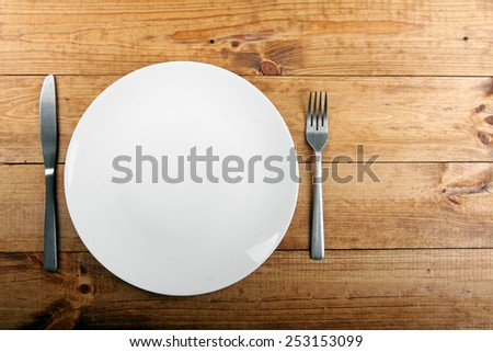 empty white plate on brown wooden table - stock photo