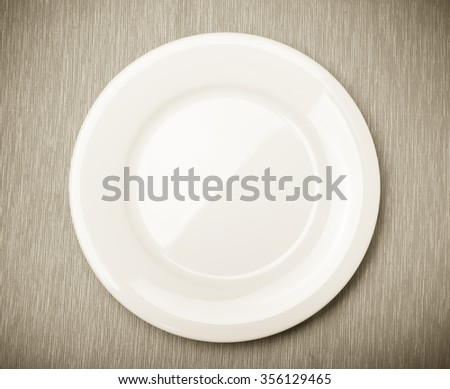 Empty white plate on grey napkin, top view. Toned. - stock photo