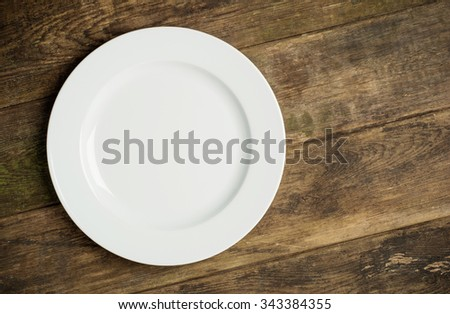 Empty white plate on rustic wooden background  - stock photo