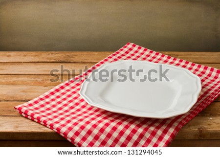 Empty white plate on tablecloth on wooden vintage table - stock photo