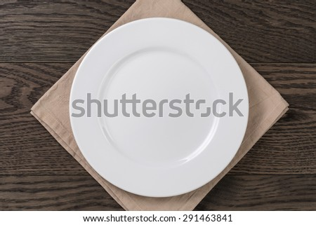 empty white plate on wood table with napkin, top view - stock photo