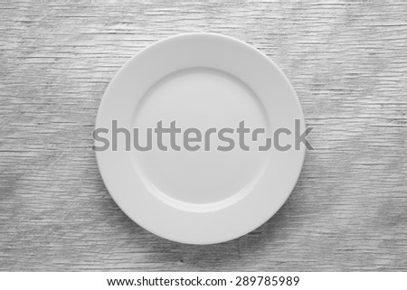 Empty white plate on wooden table close up - stock photo