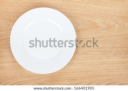 Empty white plate on wooden table. View from above - stock photo