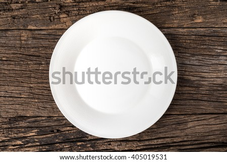 Empty white plate on wooden table with copy space,Close up  - stock photo