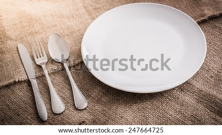 Empty white plate spoon, fork, knife on sackcloth background