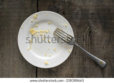 empty white plate with crumbs of grated cheese on old weathering wooden table - stock photo