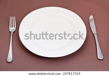 empty white plate with fork and knife set on brown background