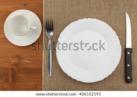 Empty white plate with knife and fork on a wooden table. Waiting for food. Home dining. Directly above view of table setting. Diet food. - stock photo